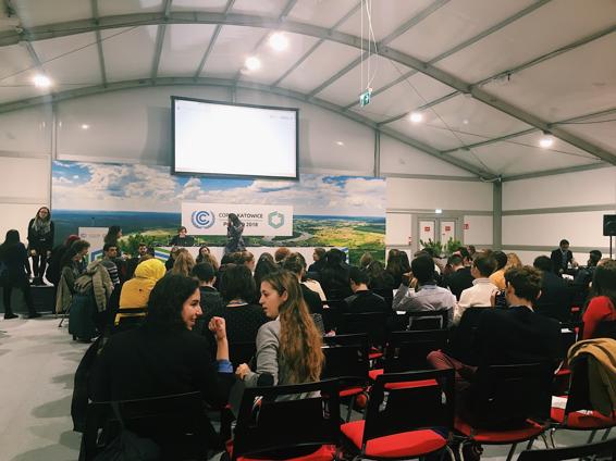 """en mindre plenarsal med ett """"sekretariat"""" längst fram på en scen. Framför scenen sitter olika representanter av det unga civilsamhället i en cirkel och agerar som """"Spokes Council"""" vilket ska vara ett forum för unga att yttra sina röster i."""