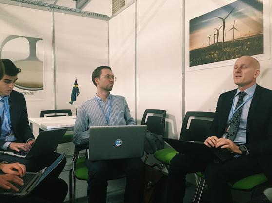 Roger sitter och pratar med några unga klimatkämpar. De sitter i en halvcirkel framför vita väggar med en plansch med vindkraftverk på.
