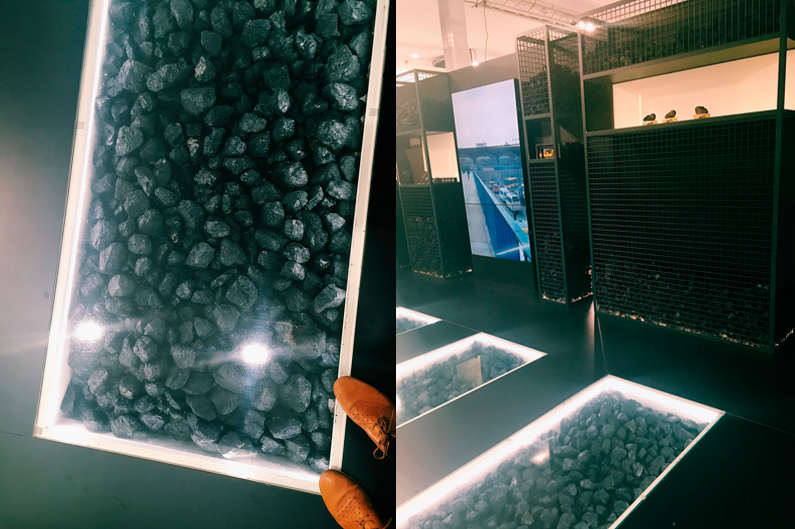 Glaslåda med kol nedgrävd i golvet och stora lådor med kol längs väggarna.