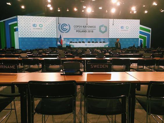 """En tom plenarsal. I förgrunden ser man ett bord med stolar där det finns en """"Sweden""""-skylt. I bakgrunden ser man scenen där presidiet ska sitta och en blågrön bakgrund med COP-loggan."""