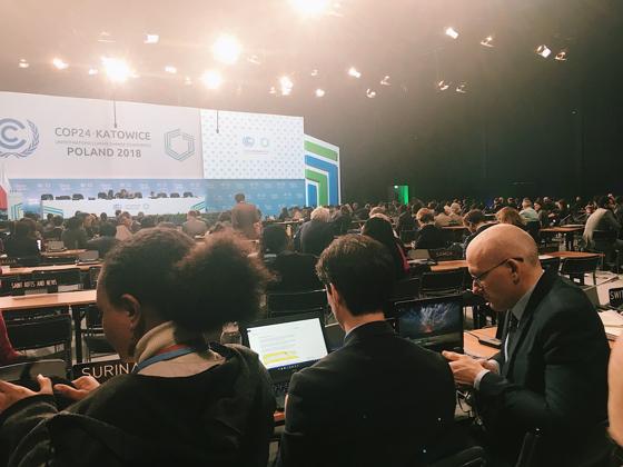 En fullsatt plenarsal med samma bakgrund som tidigare. I förgrunden ser man två av Sveriges förhandlare och våra bordsgrannar till vänster - Surinam.