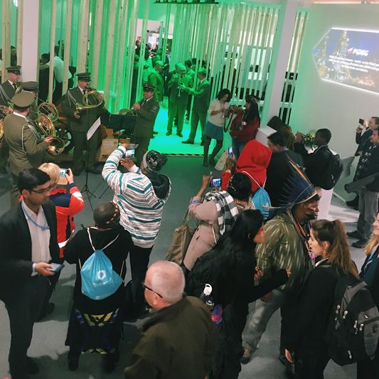 En folkmassa som står och kollar på en blåsorkester som spelar i gröna uniformer. I bakgrunden ser man träpelare som är belysta i grönt ljus. I förgrunden ser man en härlig blandning av människor med urfolk i traditionella dräkter.