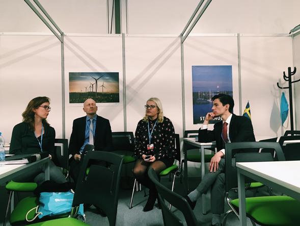 Delegationen sitter och pratar på gröna stolar. I bakgrund ser man vita väggar med upphängda planscher som visar upp Sverige på olika sätt.