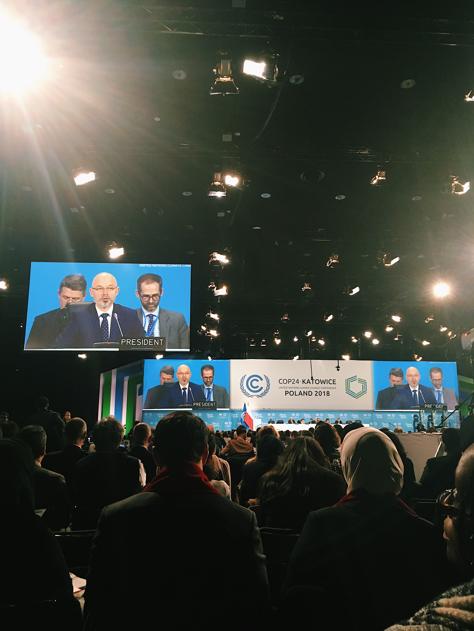 """Man ser rader av personer som alla sitter och kollar på sekretariatet som sitter längst fram framför en stor blå skylt där det står """"COP24 Katowice"""". Till vänster ser man en stor tv-skärm där Kurtyka är i bild."""