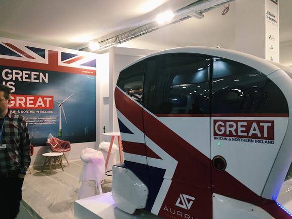 """En liten """"smartbil"""" med Storbrittaniens flagga på syns i förgrunden; i bakgrund står det """"Green is Great""""."""