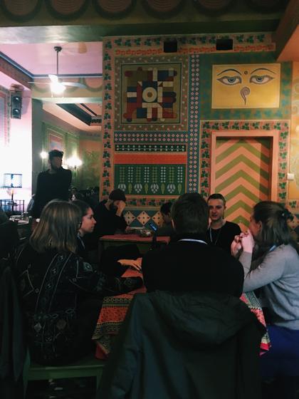 En grupp unga som sitter med ryggen mot kameran och pratar. I bakgrunden ser man färgglada väggmålningar.