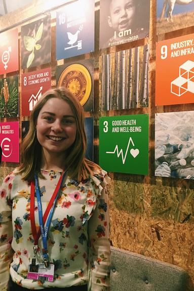 En glad Lotta framför en vägg med bilder på Agenda 2030-symbolerna.