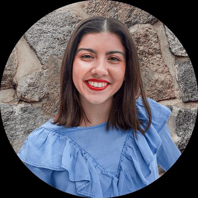 Noura står framför en grå stenvägg. Noura ler och har en blå blus på sig. Noura har rött läppstift.
